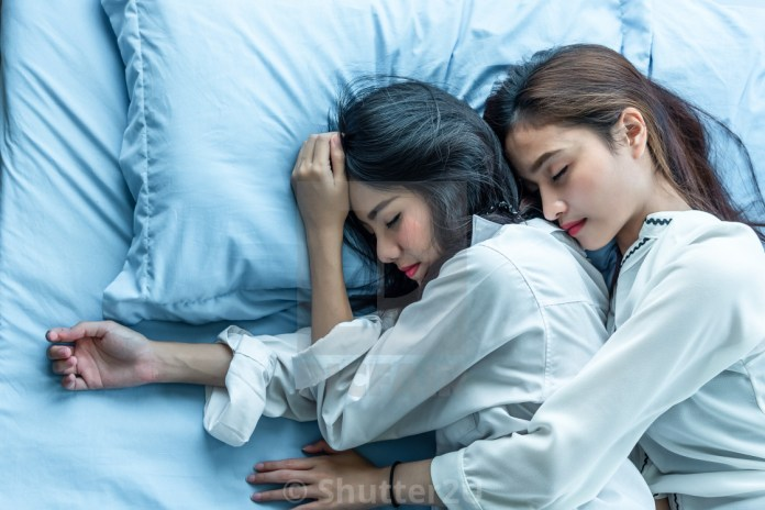 Top view of two Asian women sleeping on bed together. Lesbian lo ...