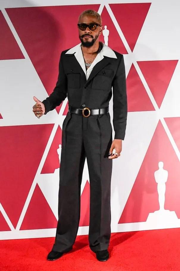 Look usado por Lakeith Stanfield no red carpet do Oscar 2021. Ele veste um macacão vintage Saint Laurent preto com lapela ampla, bolsos na altura do peito, pantalona e cintura marcada com um cinto preto de couro com fivela dourada. Por baixo do macacão está uma camisa branca com lapela larga, colar de corrente prateado e óculos escuros.