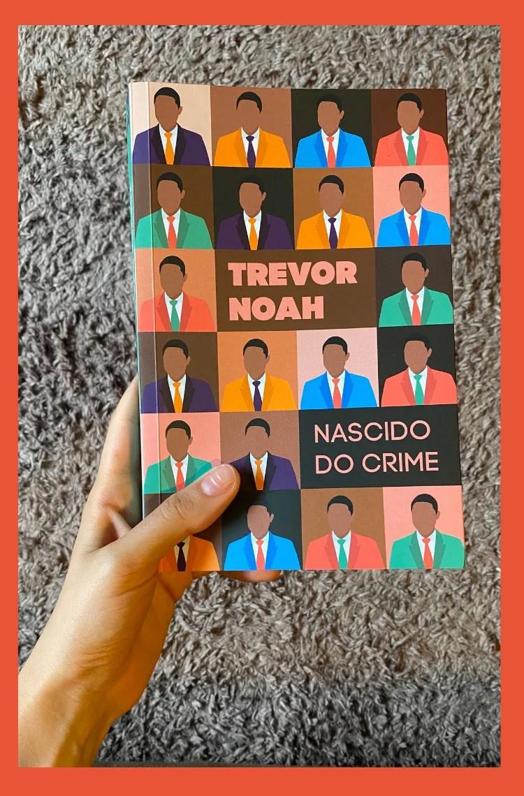 Foto vertical com moldura laranja. Na foto, uma mão branca segura o livro Nascido do crime, de Trevor Noah