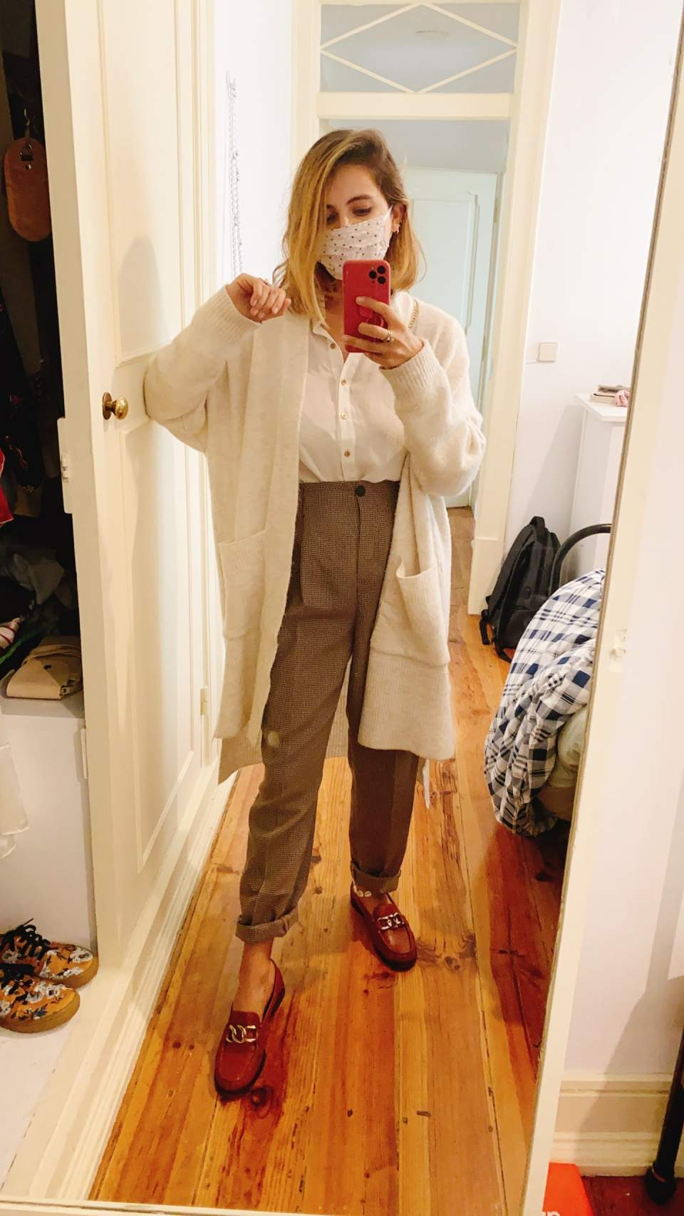 Marcie tira foto em frente ao espelho, com o celular na mão. O look é composto por uma máscara bege de flores, camisa branca com botões dourados, calça de alfaiataria com cintura bem alta marrom xadrez, cardigã branco alongado de lã e mocassim marrom de couro com argolas douradas.