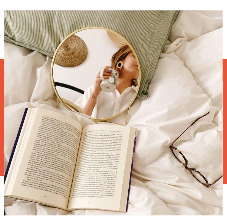 Foto com moldura branca e laranja. Uma coberta fofa está com um travesseiro com fronha listrada verde e branco, espelho redondo pequeno com moldura dourada e Marcie ao fundo com uma caneca branca na mão), um livro aberto em cima da cama e óculos de grau com estampa de tartaruga.