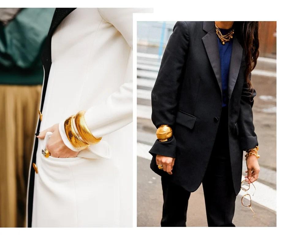 Montagem com duas fotos,  para mostrar looks de inverno 2021 com pulseiras por cima de blusas de mangas longas Foto 1 (à esquerda): uma foto detalhe do tronco, sem o rosto aparente. O look é composto por um casaco branco com lapela preta e botões dourados. Uma das mãos está no bolso, com dois braceletes dourados e um anel grande dourado. Foto 2 (à direita): uma foto de plano detalhe da região do corpo. A mulher veste uma camiseta azul-marinho com blazer preto, colares dourados e braceletes dourados por cima das duas mangas.