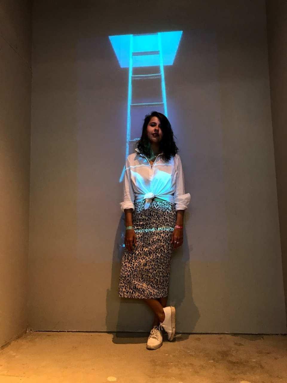 Marcie posa em frente a uma parede branca com uma escada projetada. O look é composto por camisa branca amarrada na cintura, saia lápis animal print e tênis branco.