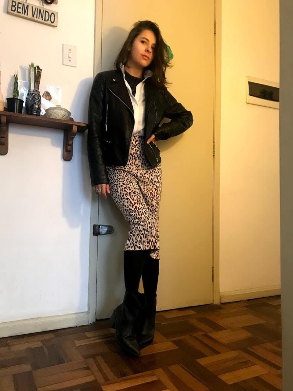 Marcie posa em frente a uma porta bege. O look é composto por camisa de gola alta listrada, usada por baixo da camisa branca, jaqueta de couro preta, saia lápis animal print, meia preta e bota preta.