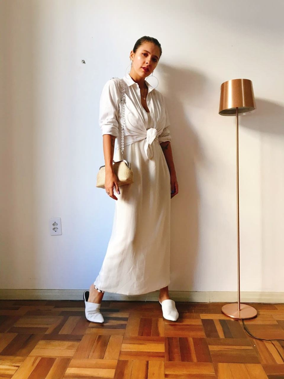 Marcie posa em frente a uma parede branca com uma luminária rosé. O look é composto por cabelos presos, brinco grande prateado, vestido branco longo com camisa branca amarrada por cima, mule branco e bolsa de palha com alça de miçangas.
