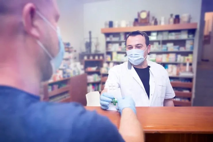 Pharmacist giving prescription to patient