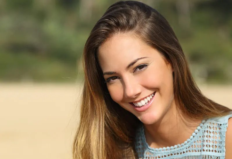 32700467 - portrait of a woman with a white teeth and perfect smile outdoors