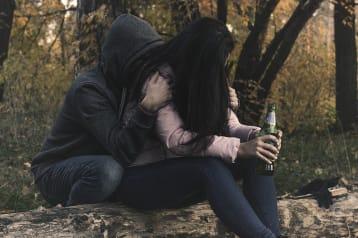 persona sosteniendo a una mujer que tiene una botella en la mano.
