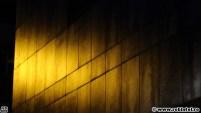 Lumina galbenă a unui bec cu sodiu iluminând un perete modern al Moară Business Center din Cluj