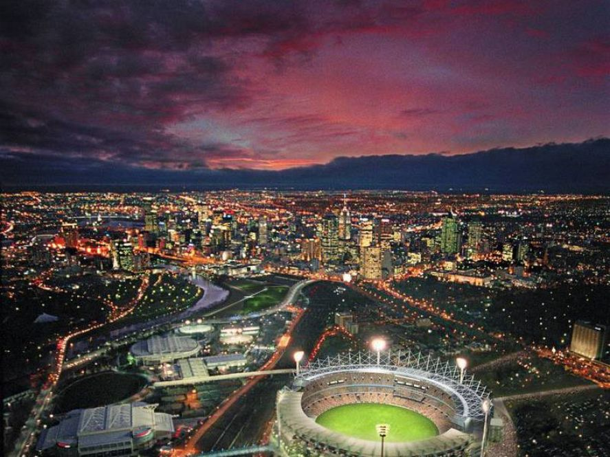 MCG Sports Stadium in front of city and deep sunset
