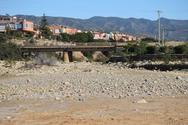 Le lit d'une rivière sèche, traversée par un pont