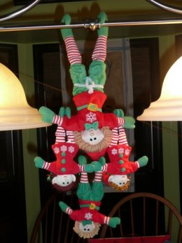 A whole family of elves hanging from a chandelier