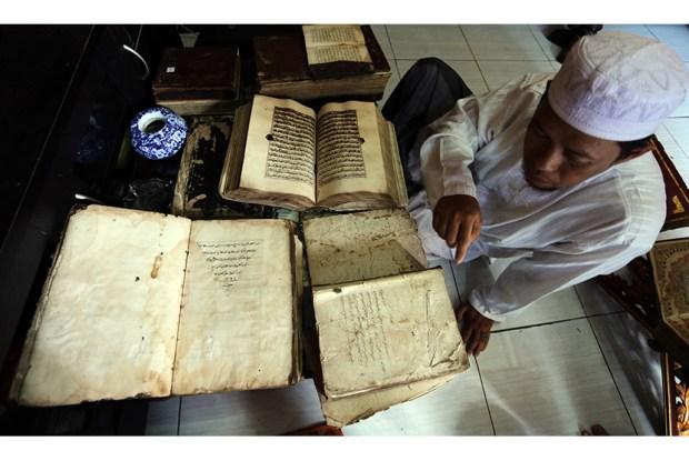 Ustadz Kemas Syarifuddin memperlihatkan koleksi Al-Quran miliknya yang berumur 250 tahun lebih dikediaman pribadinya jl Pangeran Marto, Palembang, Jumat (19/6). Al Quran tersebut dibuat tahun 1765 masehi dan diwariskan secara turun temurun oleh para leluhur. ANTARA FOTO/Nova Wahyudi/Rei/pd/15.