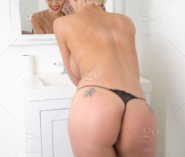 Sexy Looking Woman With Blonde Hair In Panties Applying Make Up In Bathroom Looking In Mirror While On A Phone Call Model Released