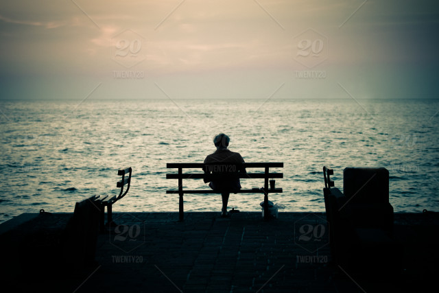 Man Silhouette Sitting On A Bench In Front Of The Sea On Sunset And Reading  A Book stock photo f2b0086b-f1a3-44a8-91e1-51cd44d075d4