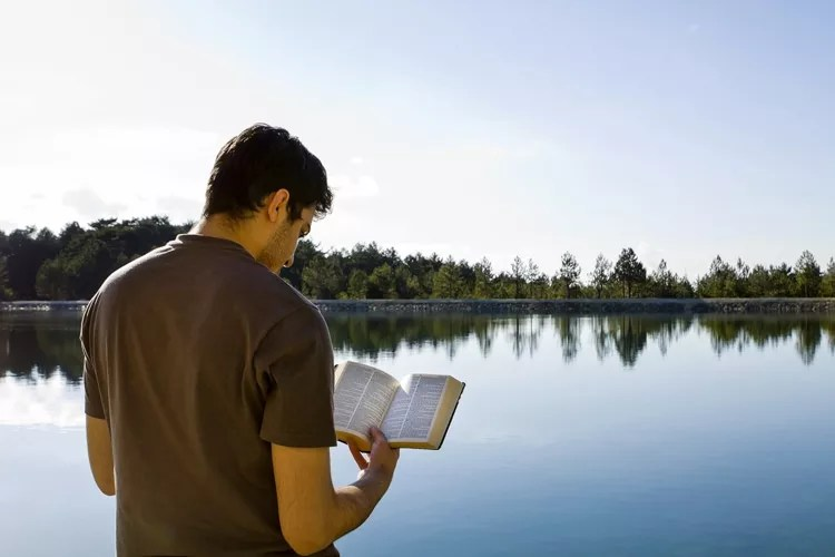 Man reading bible by a lake