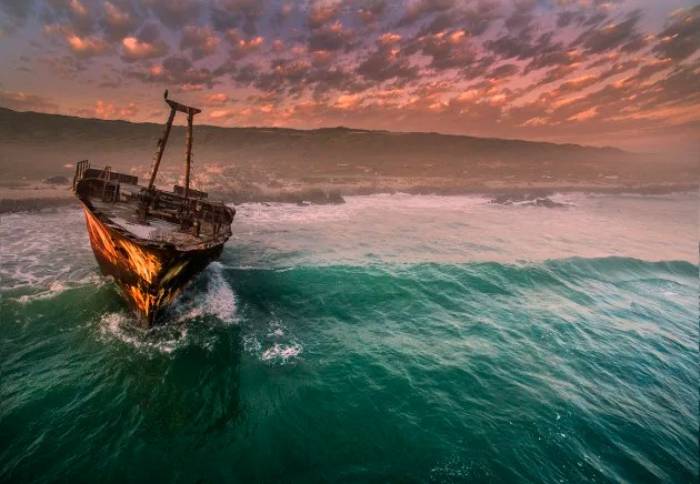 Ship Wreck at L'Agulhas by Dirke Heydenrych. A dramatic sunset is the perfect backdrop for this shipwreck off the Cape L'Algulhas headland in South Africa.
