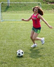 Teen Girl Kicking Soccer Ball