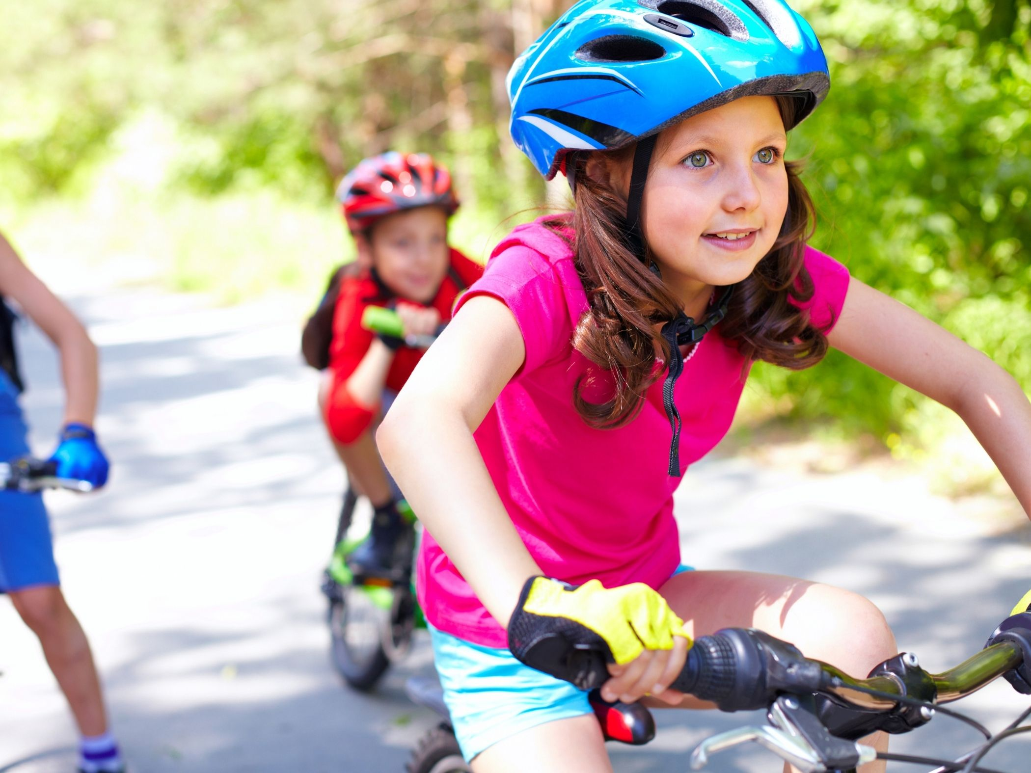 Young girl riding a bicycle outside on a paved trail