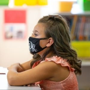student with monogrammed mask sitting at her desk with her arms crossed