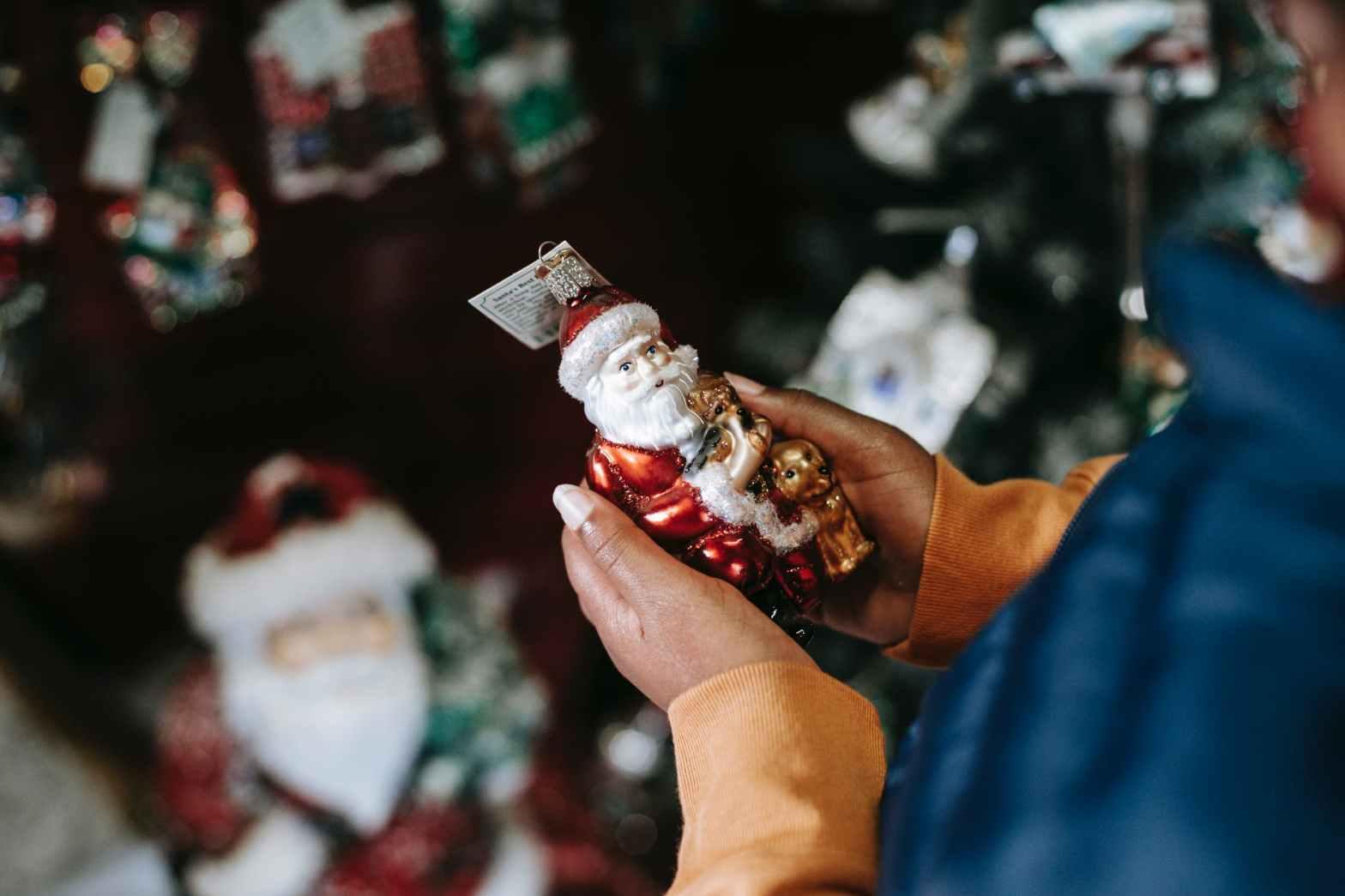 crop black person with decorative santa claus in shop