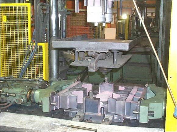 Large piece of machinery with three rows of intertwining slabs of metal and an overhanging sheet of metal pressing down