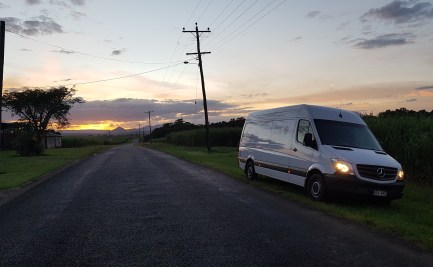 A road stretches out to the horizon, the sun setting behind clouds. A white van sits at the side, headlights on.