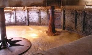 Large circular mixing blade in a tank of brown liquid