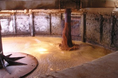Large circular mixing blade in a tank of brown liquid