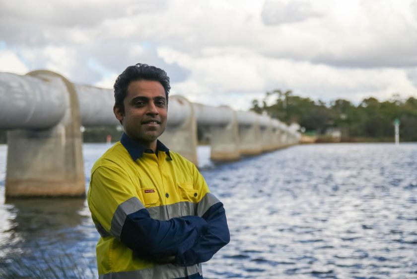 Male in hi-vis in front of elevated pipeline crossing a river