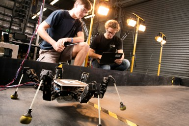 6 legged robot learning to walk, while researchers observe its walking pattern