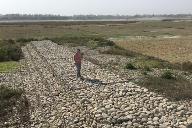 A man standing on a gabion wall