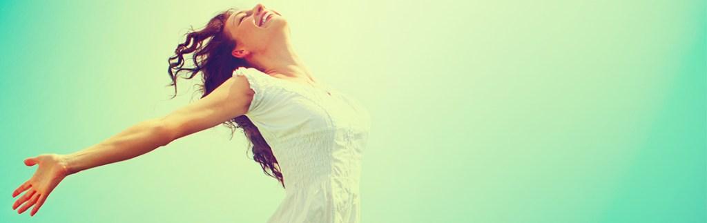 A woman spreads her arms joyfully