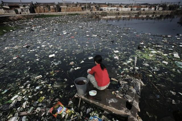Une-femme-fait-sa-lessive-dans-un-étang-pollué