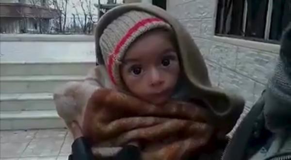 Un tout-petit est soutenu devant la caméra dans cette image d'une vidéo dite tournée à Madaya le 5 janvier 2016