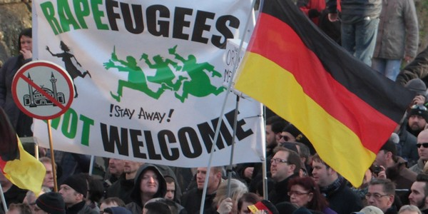 """Right-wing demonstrators hold a sign """"Rapefugees not welcome - !Stay away!"""" and a sign with a crossed out mosque as they march in Cologne, Germany Saturday Jan. 9, 2016. Women's rights activists, far-right demonstrators and left-wing counter-protesters all took to the streets of Cologne on Saturday in the aftermath of a string of New Year's Eve sexual assaults and robberies in Cologne blamed largely on foreigners. (AP Photo/Juergen Schwarz)"""