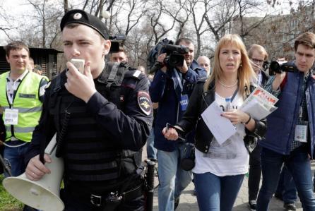 Reuters Coordinatrice du mouvement Open Russia, Maria Baronova (deuxième à droite) entourée de journalistes et de représentants des forces de l'ordre.