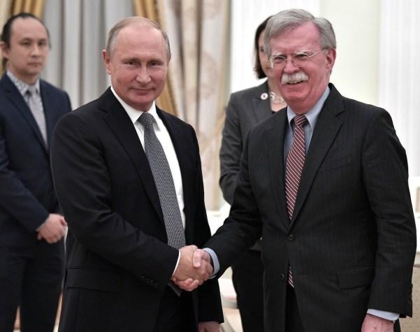 Le président russe Vladimir Poutine, à gauche, serre la main du conseiller américain pour la sécurité nationale John Bolton avant leur réunion au Kremlin à Moscou le 23 octobre 2018