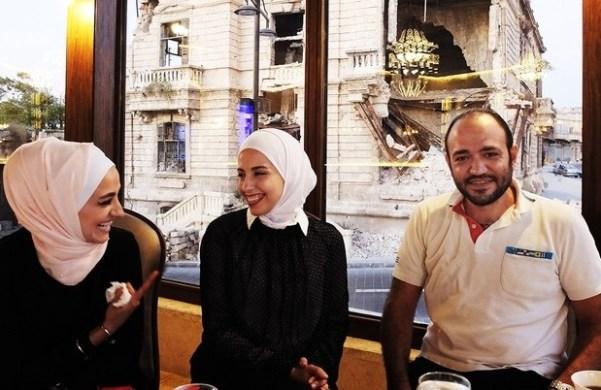 Dani Ajam, propriétaire d'un restaurant, et sa famille : les décombres en arrière-plan sont l'emplacement d'un futur hôtel (MEE/Katharine Cooper)