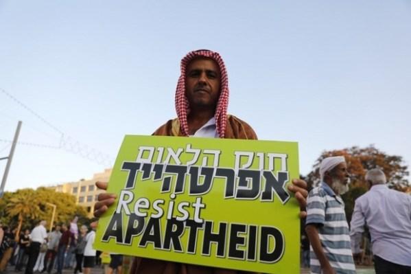 Un citoyen palestinien d'Israël porte une pancarte pour protester contre l'apartheid israélien à Tel Aviv, le 11 août 2018 (AFP)