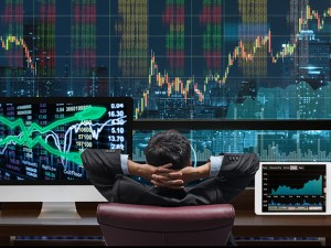 Back side of sitting businessman who is looking at stock market exchange graph over the cityscape on the big screen background and desktop computer with tablet showing the trading graph, trade concept