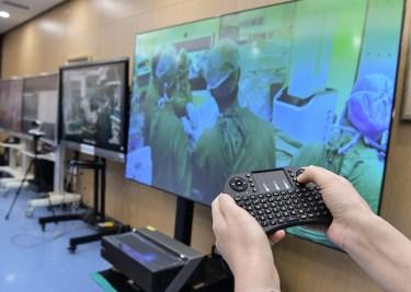 Un assistant d'opération contrôle un système de diffusion en direct 5G+ à vision libre pour fournir une référence visuelle aux médecins de l'hôpital affilié de l'université de Qingdao, dans la province du Shandong (est de la Chine)