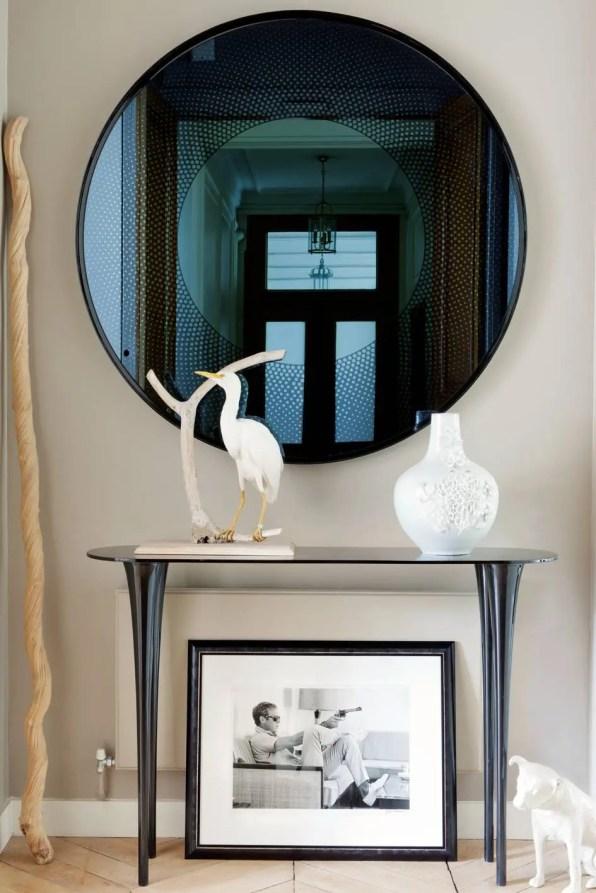 Damien a rajouté sa touche dès l'entrée, dominée par le miroir « You Are Beautiful » et la console « Stand By Me, » qui font partie de sa collection pour Pouenat. Photo de Steve McQueen par John Dominis.