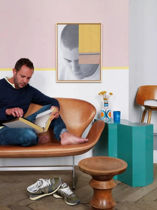Jean-Christophe Aumas assis sur un sofa en cuir d'Arne Jacobsen. Devant, un guéridon en chêne de Tom Dixon ; au mur, autoportrait ; l'élément peint à droite provient d'une vitrine réalisée pour Petit Bateau.