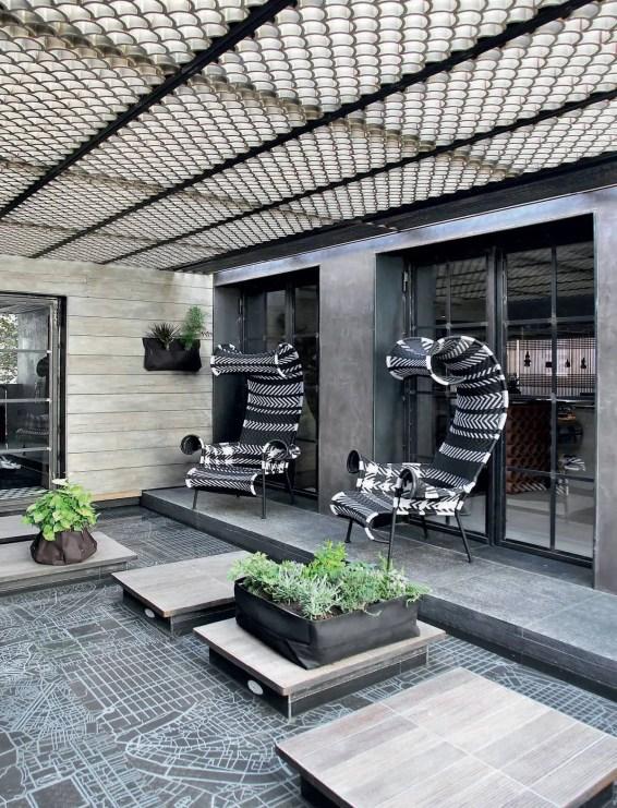 Sur la terrasse, deux fauteuils « Shadowy » de Tord Boontje pour Moroso à la structure en acier et aux motifs tressés par des artisans africains, invitent à la détente. Une treille en métal façon « écailles de poissons » fait écran aux rayons du soleil.