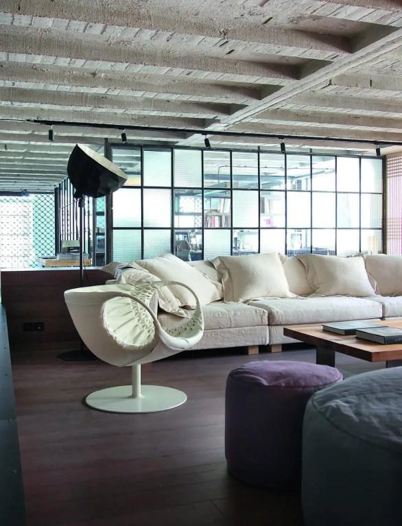 Un fauteuil blanc de Patricia Urquiola pour Moroso trône élégamment entre un canapé de la collection Diesel et des poufs édités par Morphos. Table basse créée par Ese. Lampadaire « Rock » de Diesel pour Foscarini