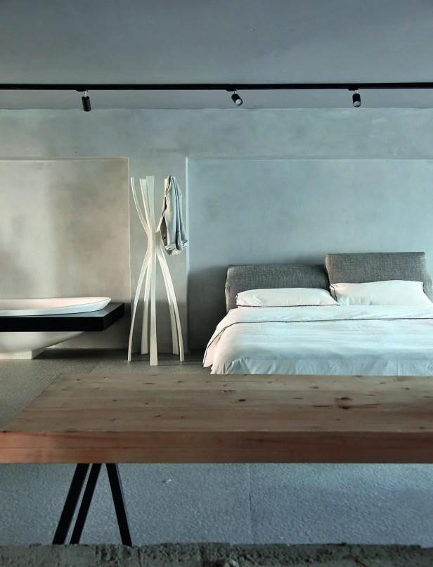Esprit loft oblige, un coin salle de bains est aménagé dans la chambre où trois matériaux se juxtaposent : au mur du béton, au sol du carrelage et du bois pour le mobilier.