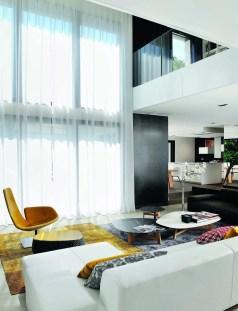 L'architecte d'intérieur floute la ligne tendue de la baie vitrée dans une apaisante cascade de voilage et réconforte le canapé « Lowland » de Patricia Urquiola pour Moroso d'un jeu de formes et de matières créé à partir de l'association d'un tapis de soie gris et d'un tapis en laine safran (Moroso).