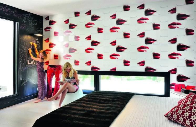Avec ses fenêtres abaissées au sol, la chambre de la fille ainée joue la modernité absolue renforcée par un papier peint pour le moins embrasé : « Kisses for Ever » édité par Elitis.