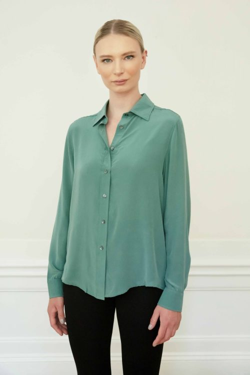 Blond girl wearing a green silk shirt with buttons